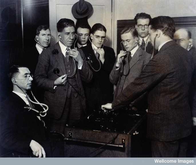 Doctors or medical students listening to their heartbeats using a multiple stethoscope. Photograph. 1920's By: Central News.Published: [192-]