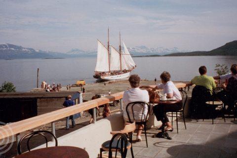 Bilde: Folk på terrassen utenfor Trondenes Historiske Senter. Anleggsbrakker og Anna Rogde i bakgrunnen. Foto: Øystein Normann/Sør-Troms Museum.