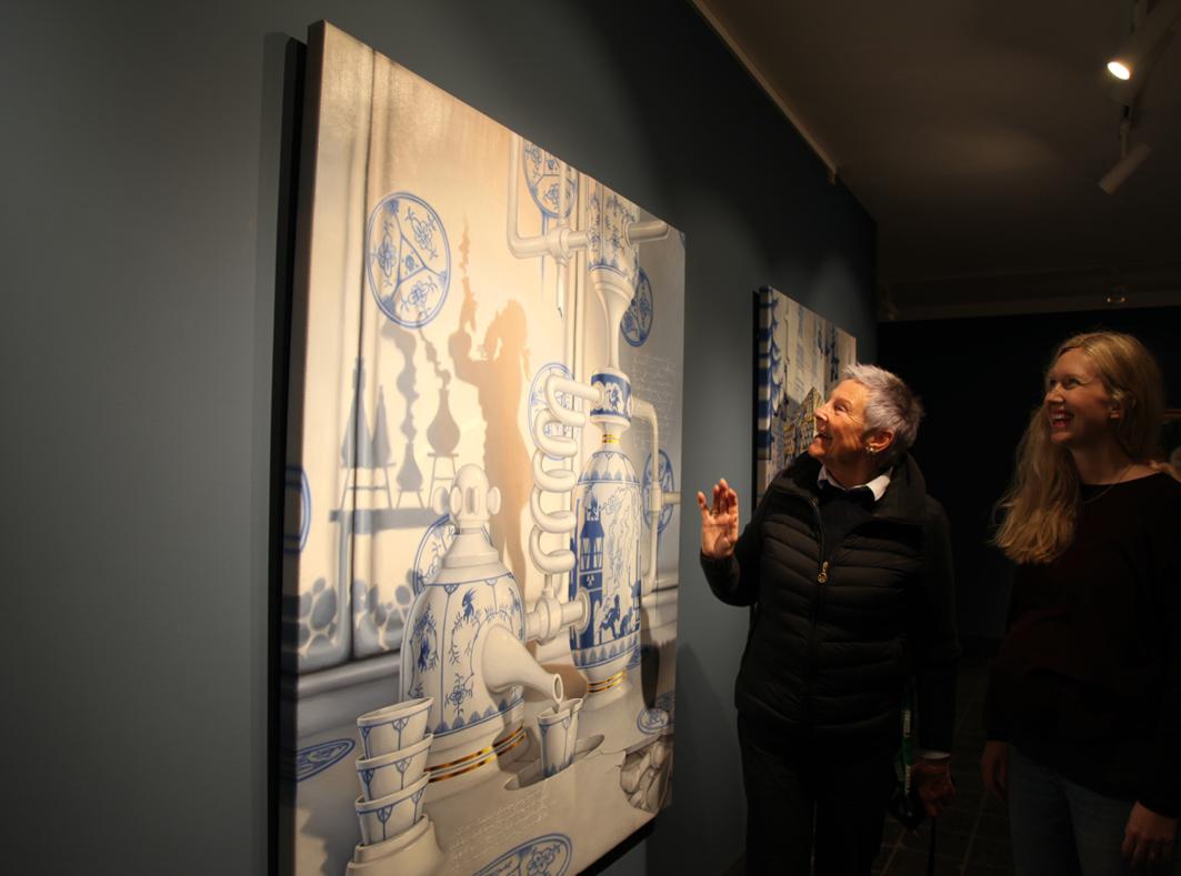 BLAA TRÅD: Årets kunstutstilling har fått navnet «Hjemmets skatter» og har porselen som en «blå tråd». Kurator Sandra Lorentzen (t.h.) og direktør Tone Steinsvik er særlig begeistret for den lokale kunstneren Bjørn Båsens fremstilling av det gamle verkets koboltproduksjon, et bilde som er malt spesielt til årets utstilling.