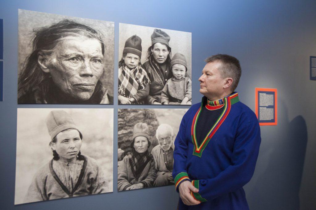 FOLK har fulgt i forskernes fotspor i Tysfjord og gitt ordet til forskningsobjektenes etterkommere. Bildene på veggen viser: Inga Andersdatter, født i Sverige ca. 1830, IngerNikolaisdatterTjikkom(f. 1879), med barna Sara og Peder, Tjierrek-Ánne(AnneAbmutsdatterKurak)(1882–1948) og Finne JohnsenRáhka(1830–1918). Foran dem står Lars Magne Andreassen, direktør ved Árran lulesamisk senter. Foto: Åsa Maria Mikkelsen.
