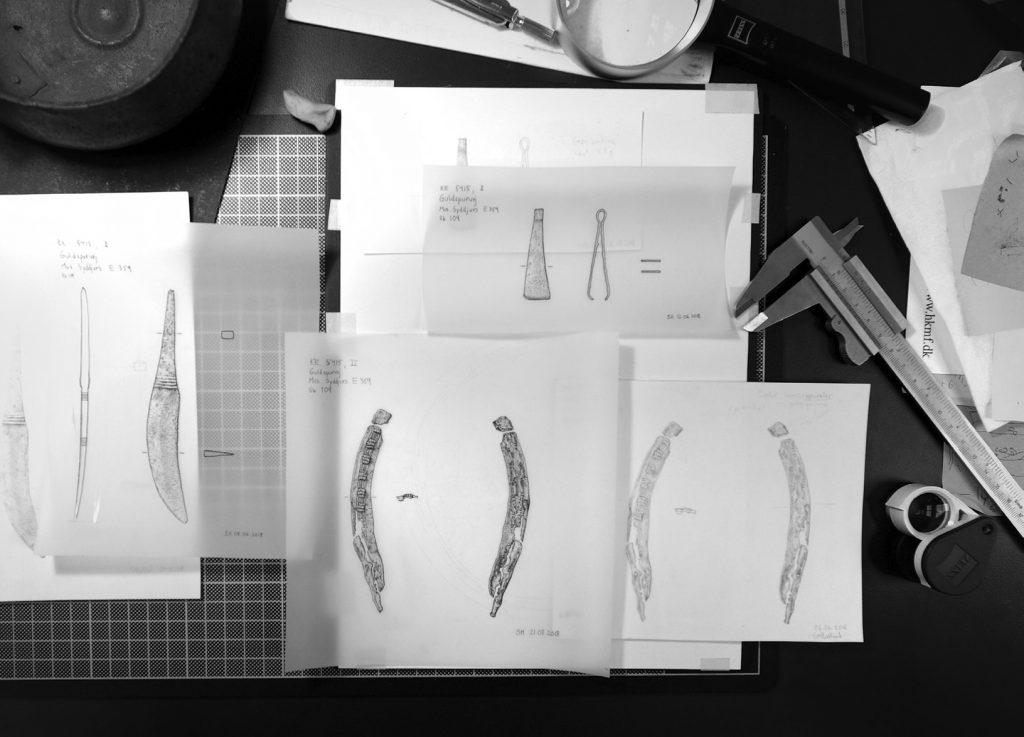 ARBEIDSPULT: Sol Hallsets tegninger av blant annet en barberkniv og pinsett i bronse, samt etui av lær, fra området Randers Amt i Danmark. Foto: Thomas Kolbein Bjørk Olsen