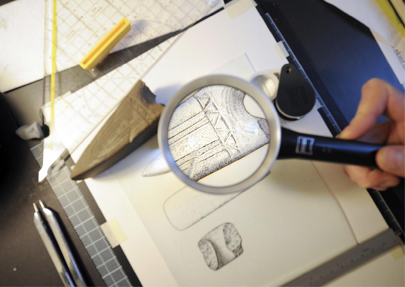 STRIDSØKS: Tegningene består av prikker og streker som gjenskaper objektenes detaljer på papir med 0,1 millimeters nøyaktighet. Her en stridsøks i stein, fra Randers Amt, tegnet av Sol Hallset. Foto: Thomas Kolbein Bjørk Olsen