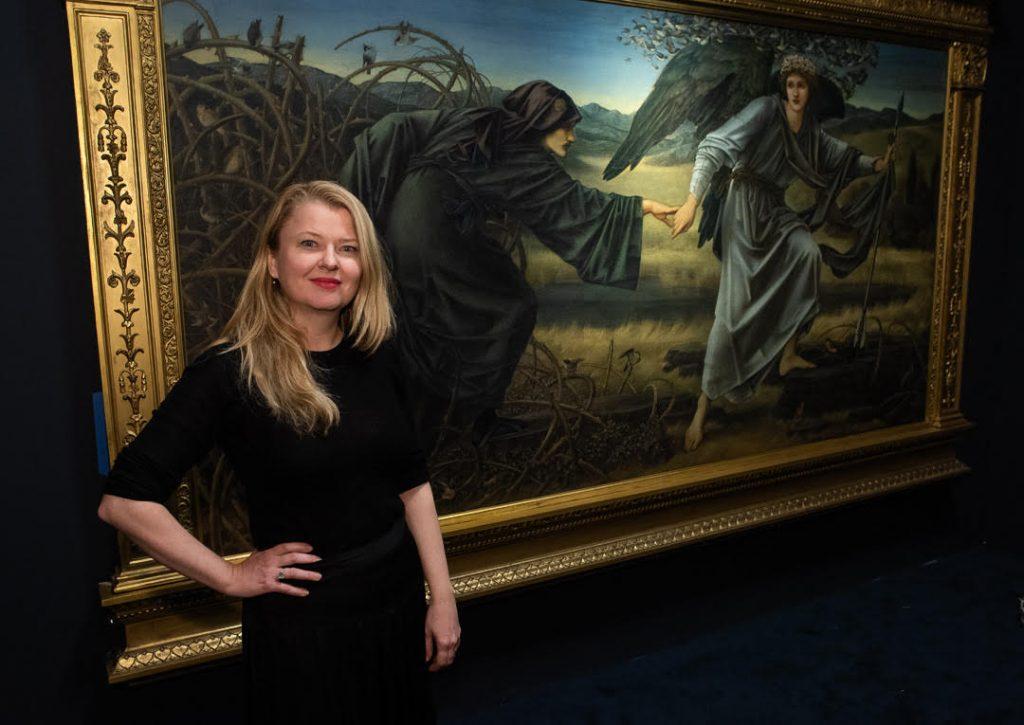 Portrettfoto av kvinne foran et maleri på museet (Kode)