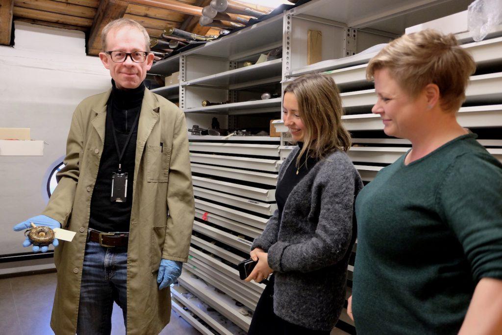 Foto frå magasinet i Forsvarsmuseet: ein mann og to damer, arkivskap i bakgrunnen