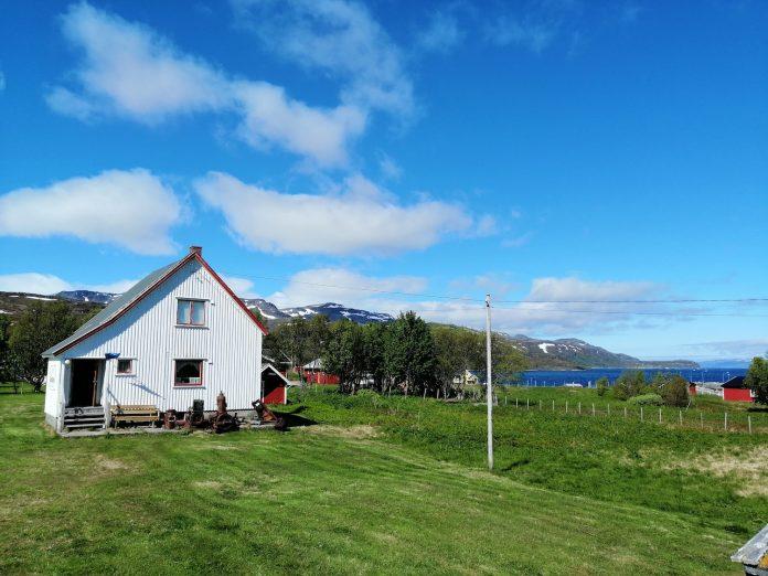 Foto av landskap med et hvitt trehus med skråtak