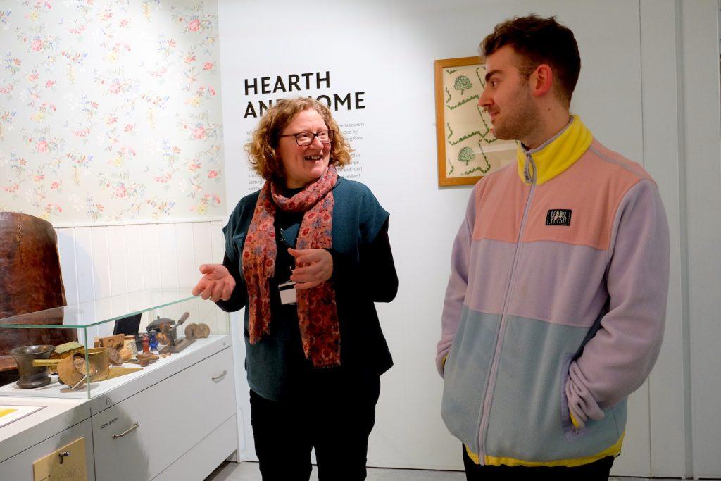 Foto av ei kvinne og ein mann som står og prater inne i eit utstillingslokale