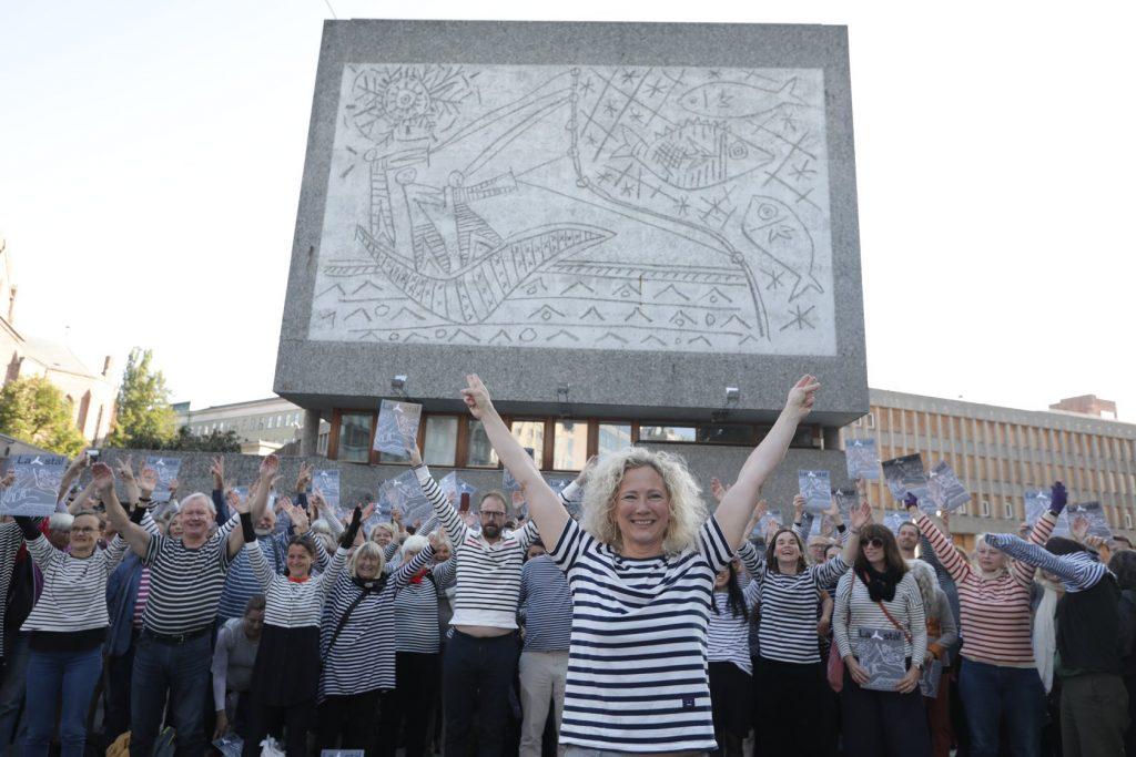 Foto av gavlveggen til Y-blokka med demonstranter med stripete genser foran. I front, Henie Onstad kunstsenters direktør Tone Hansen. Alle med hendene i været (Y-form)