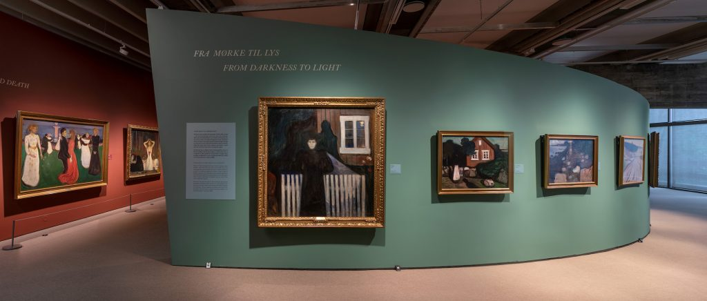 Bilde av avrunda, grøn utstillingsvegg inne på Kode. Fleire Edvard Munch-maleri på veggen.