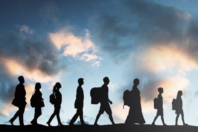 Silhuett av flyktninger, åtte personer med bagasje som går på rekke