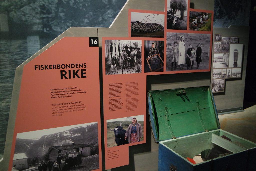 """Veggplansjer med tekst, fotografier og en åpen kiste. En overskrift på veggteksten er """"Fiskerbondens rike"""""""