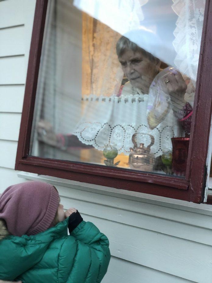 En gammel dame inne bak et vindu som er litt åpent, hvor hun snakker med et barn som står utenfor vinduet
