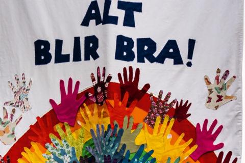 """Utsnitt av fane med teksten """"Alt blir bra"""", regnbuemotiv dekorert med barnehender klipt ut av stoff"""