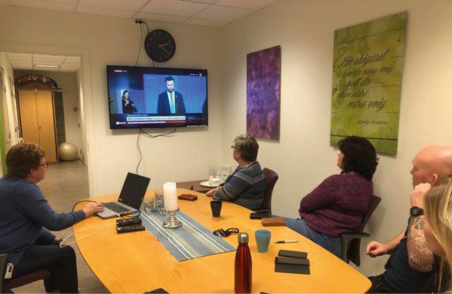Fire personer rundt et møtebord ser på tv-skjerm som viser pressekonferanse