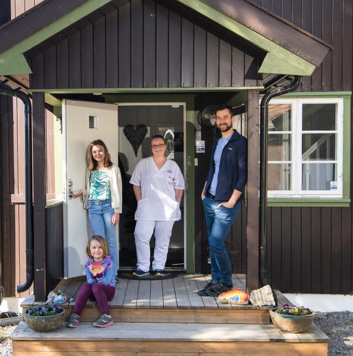 Portrett av mann, kvinne i sykepleierantrekk og to døtre, i døråpningen til huset sitt