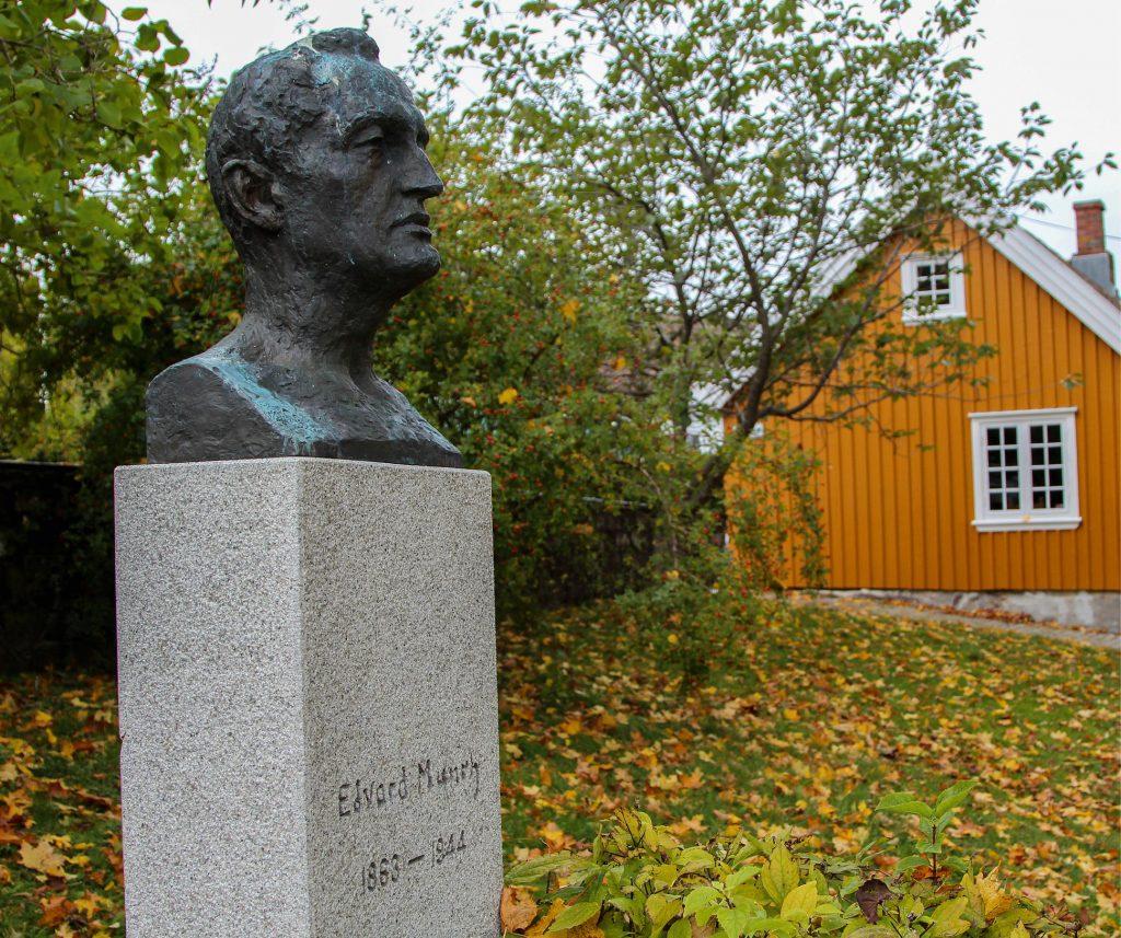 Byste av Munch i forgrunnen, hus i bakgrunnen