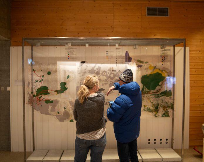 Bilde fra utstillingen. To personer ser på et kart i et monter
