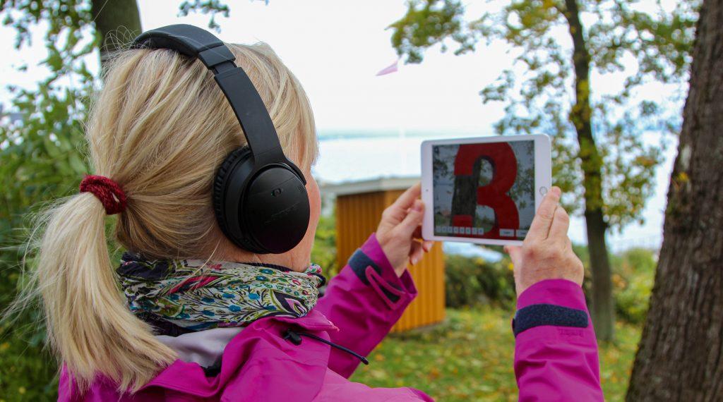 Person som holder en iPad opp mot omgivelsene / naturen