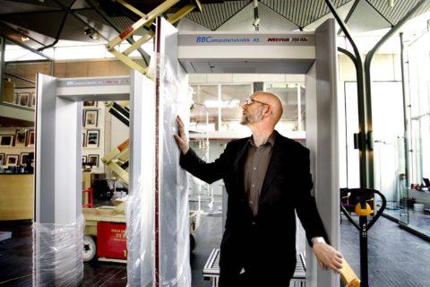 Mann som står inni en røntgenportal under utpakking