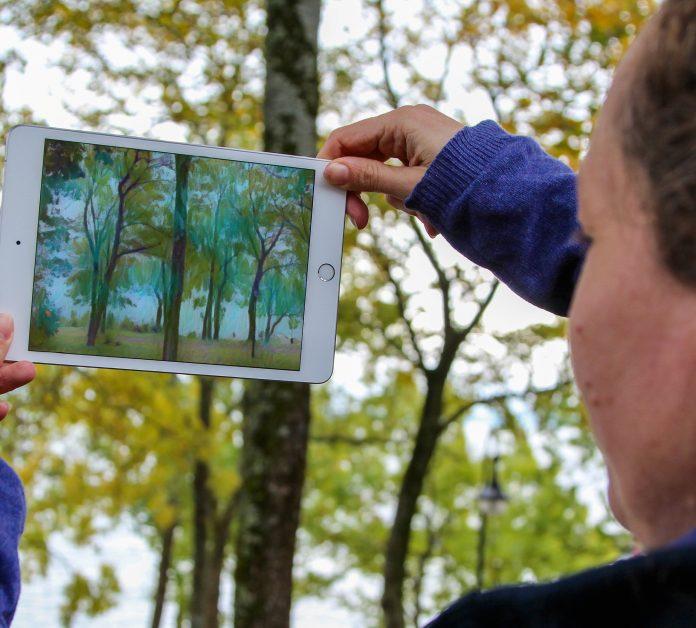 iPad som holdes opp mot en skog. iPaden viser den samme skogen men transformert så det ser ut som om den er malt