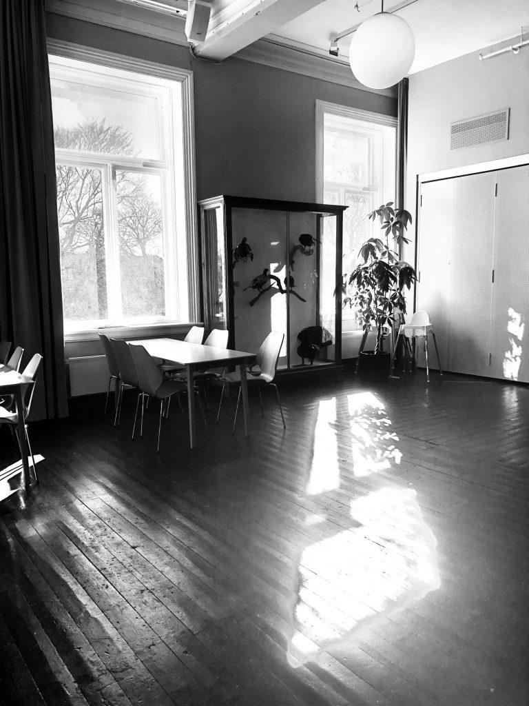 Svart hvitt og i motlys, rom med sollys som faller inn, et monter, noen bord og stoler