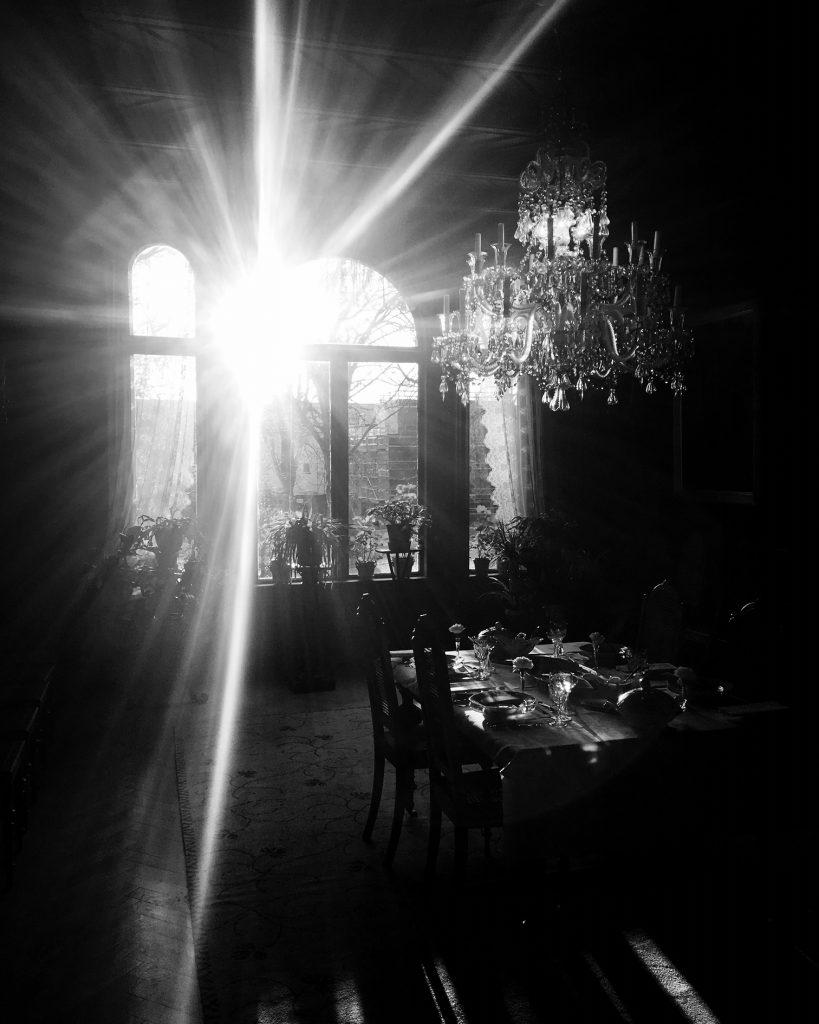 Svart hvitt og i motlys. Så vidt synlig stue med lysekrone og spisebord
