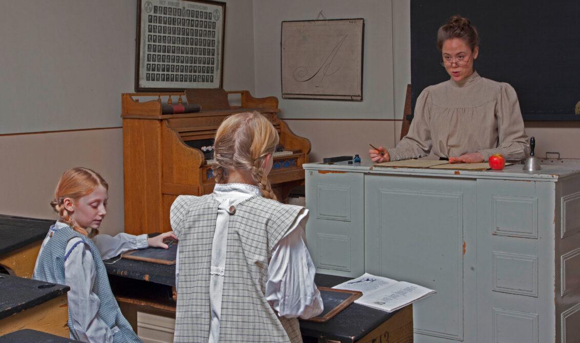 Gammeldags klasseværelse med lærer og to elever