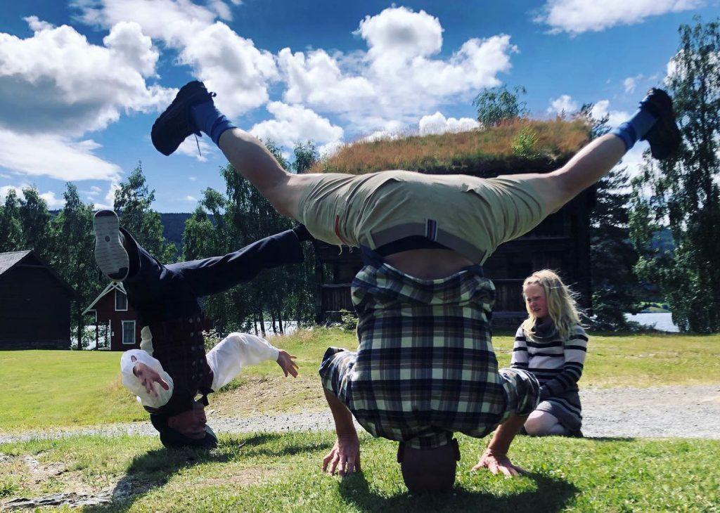 To menn står på hodet ute på gresset i et friluftsmuseum