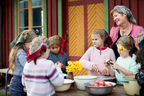 Fem barn og en voksen med skaut skreller poteter utenfor en eldre bygning