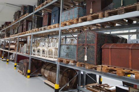 bilde av museale kister på hyller i museumsmagasin