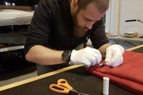 Mann med hvite tøyhansker som syr på et stykke rødt tøy