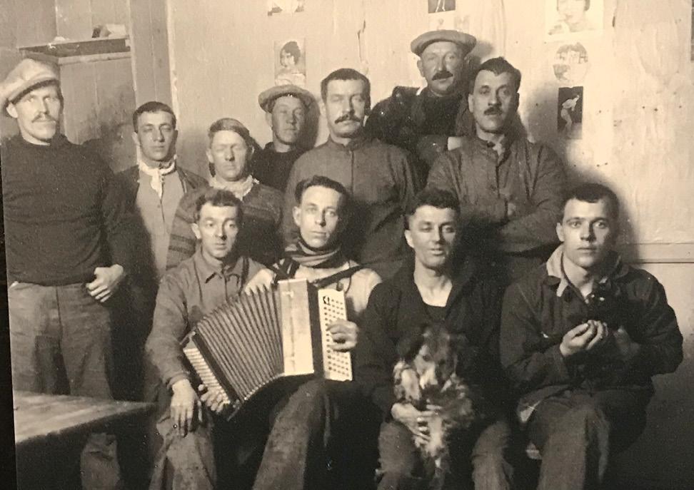 Sv-foto av en gjeng unge menn - en med trekkspill og en med en hund på fanget