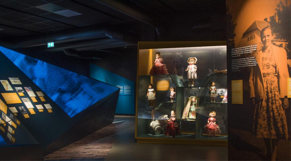 Foto fra utstillingsrom med bl.a. et monter med dukker i