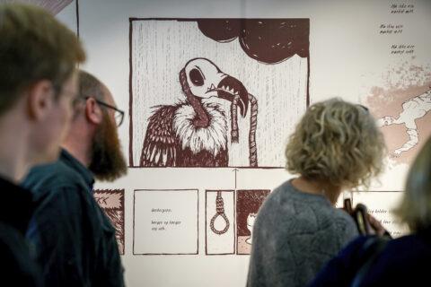 Bilde fra utstilling med illustrasjon på vegg og mennesker som ser på denne