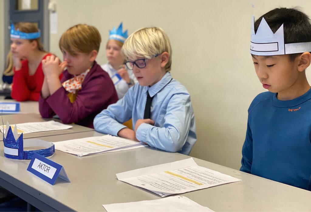 Fem barn ved siden av hverandre med papirer foran seg. Navnelappe med Aktor står på pultene og barna ser konsentrerte ut
