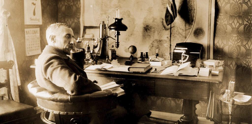 Historisk foto av Roald Amundsen ved kontorpulten sin