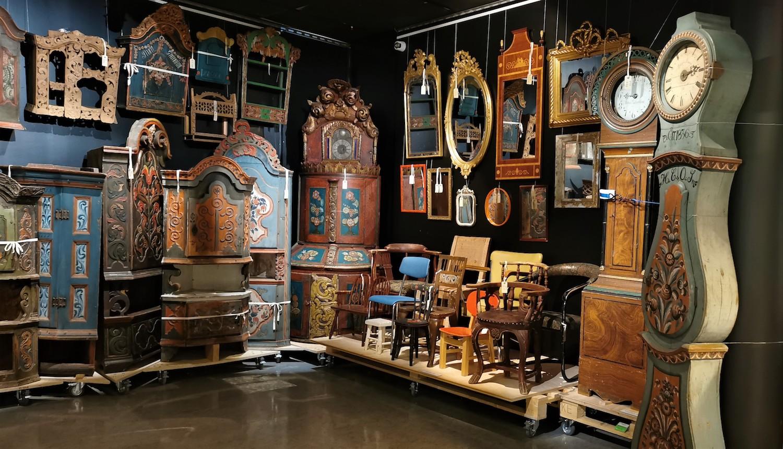 Rom hvor speil, gulvklokker og rosemalte skap står tett i tett på paller med hjul og med synlig registreringsnummer