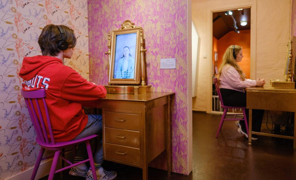 to ungdommer sitter foran hver sin skjerm i rom med rosa og oransje vegger