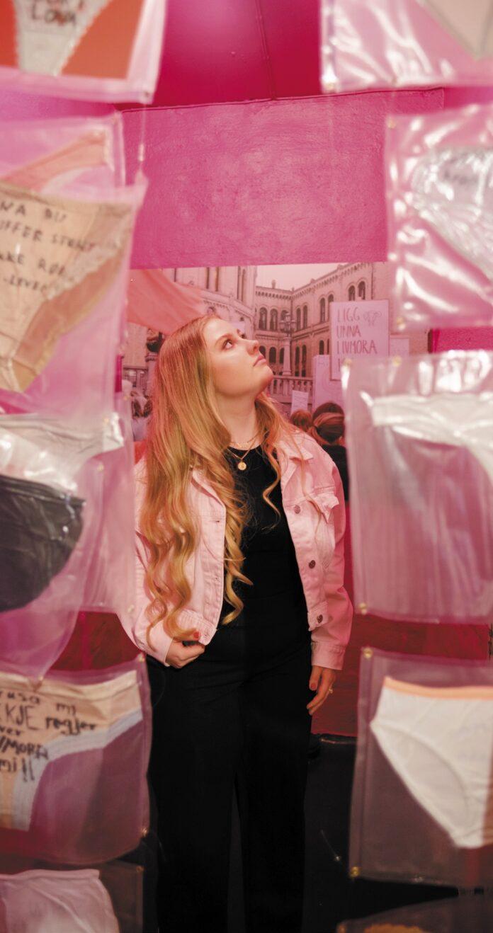 ung kvinne omgitt av rosa bakgrunn og opphengte truser med protesttekster på