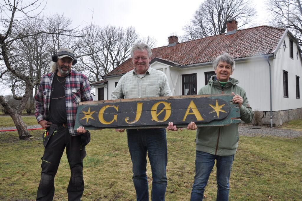 """Tre menn holder et stort skilt med teksten """"Gjøa"""" inngravert"""