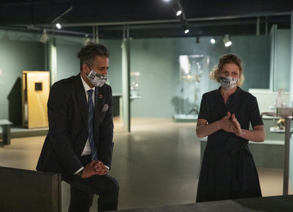 En mann og en kvinne, begge med munnbind, i et utstillingsrom