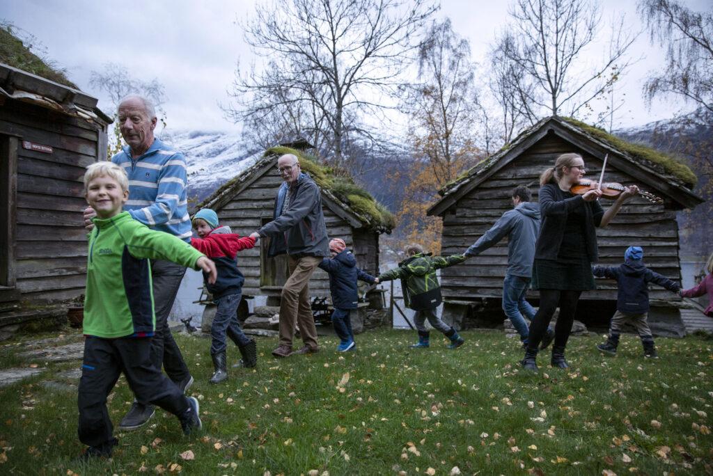 Ute i eit bygdetun, kvinne spelar hardingfele medan ei gruppe born og eldre held kvarandre i hendene og dansar rundt felespelaren