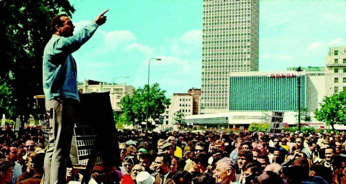 Mann med løftet arm taler på Speakers' corner, folkehav i bakgrunnen