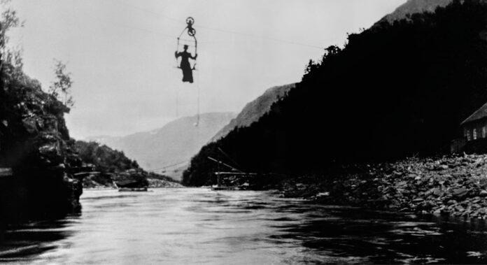 Historisk bilde av kvinne i en taubane over en fjord